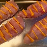 Step 3. Cheddar cheese arranged in pockets of chicken before cooking.