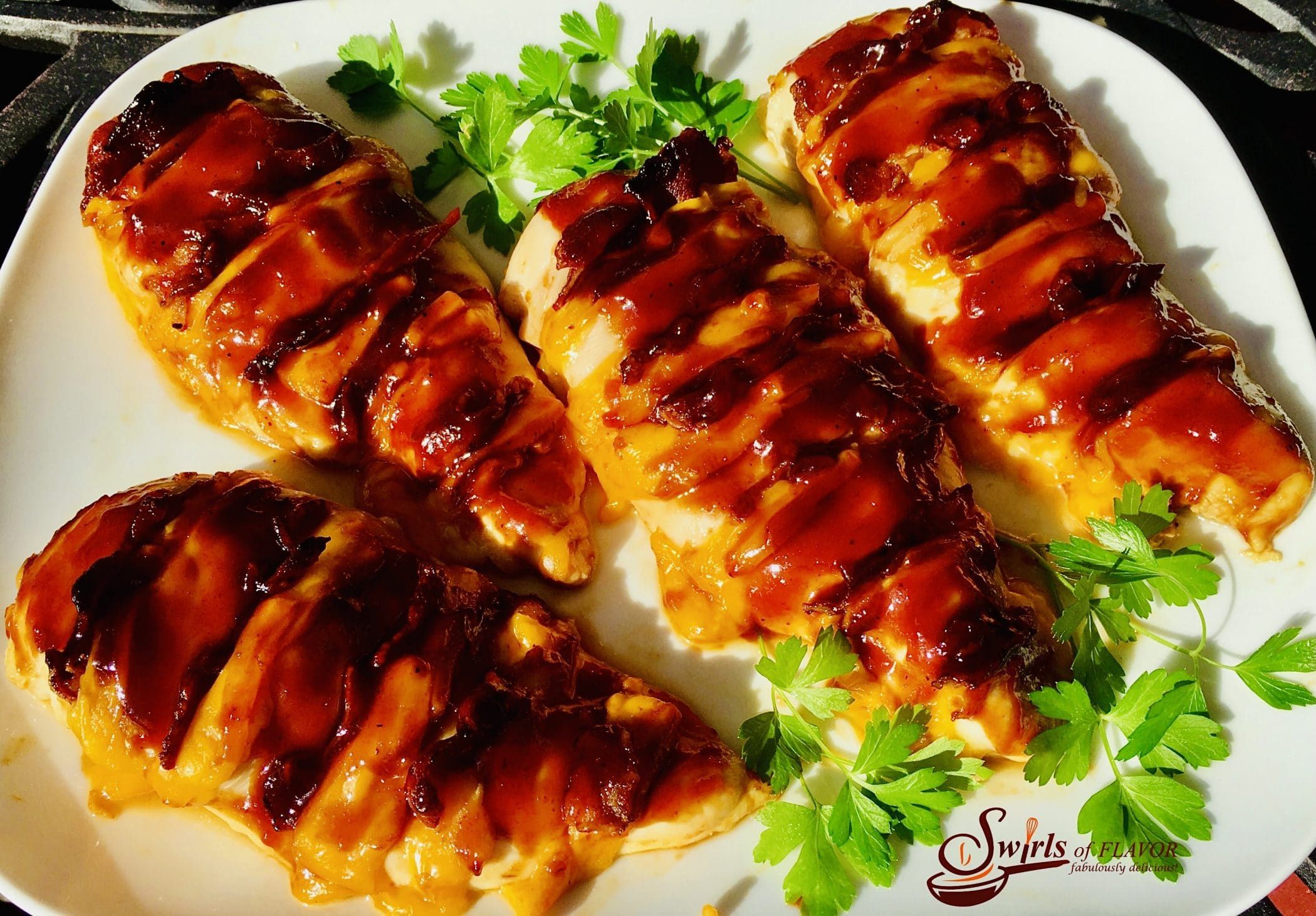 overhead photo of hasselback chicken with bacon and cheese and fresh herbs