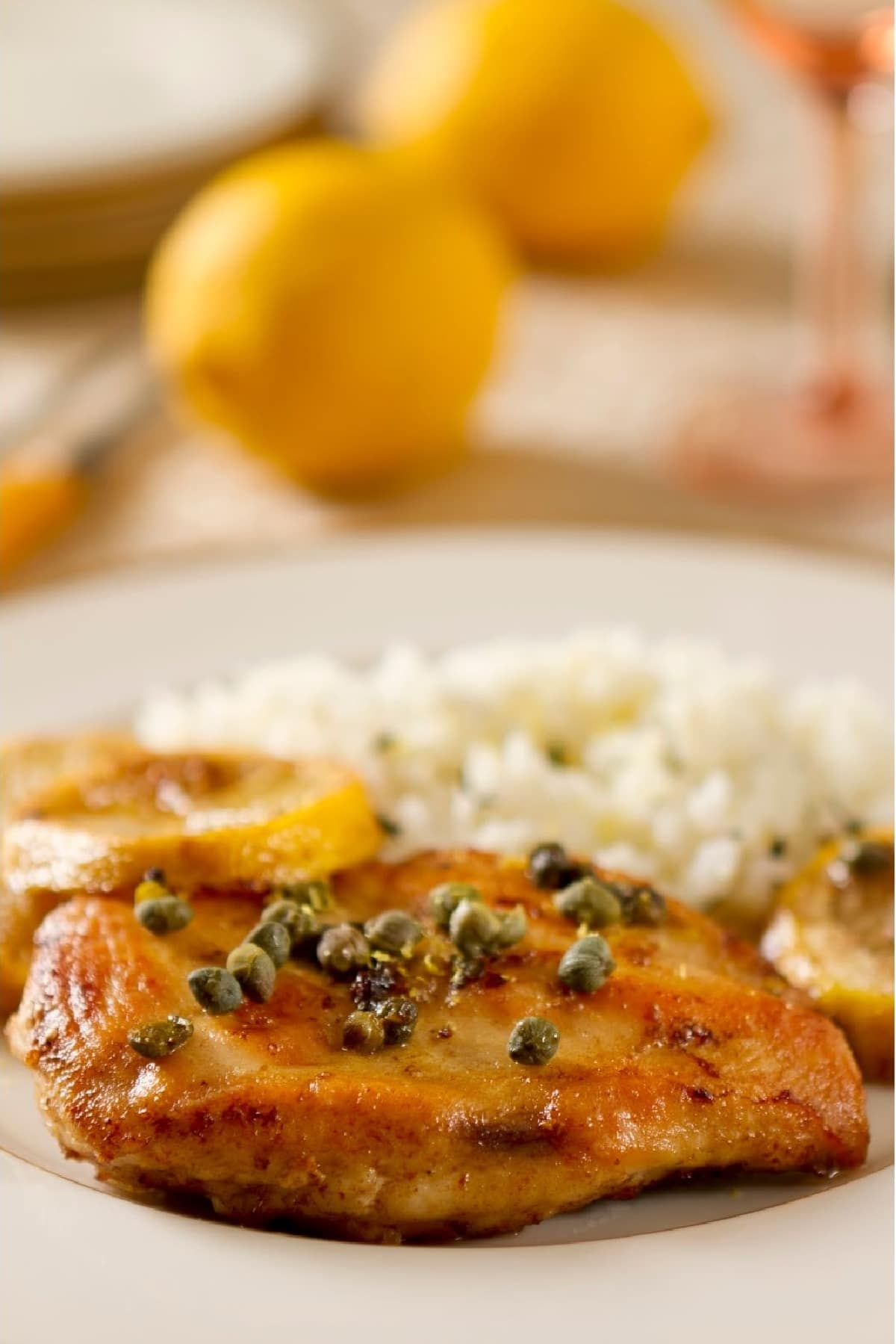 chicken with lemon and capers on a plate with rice