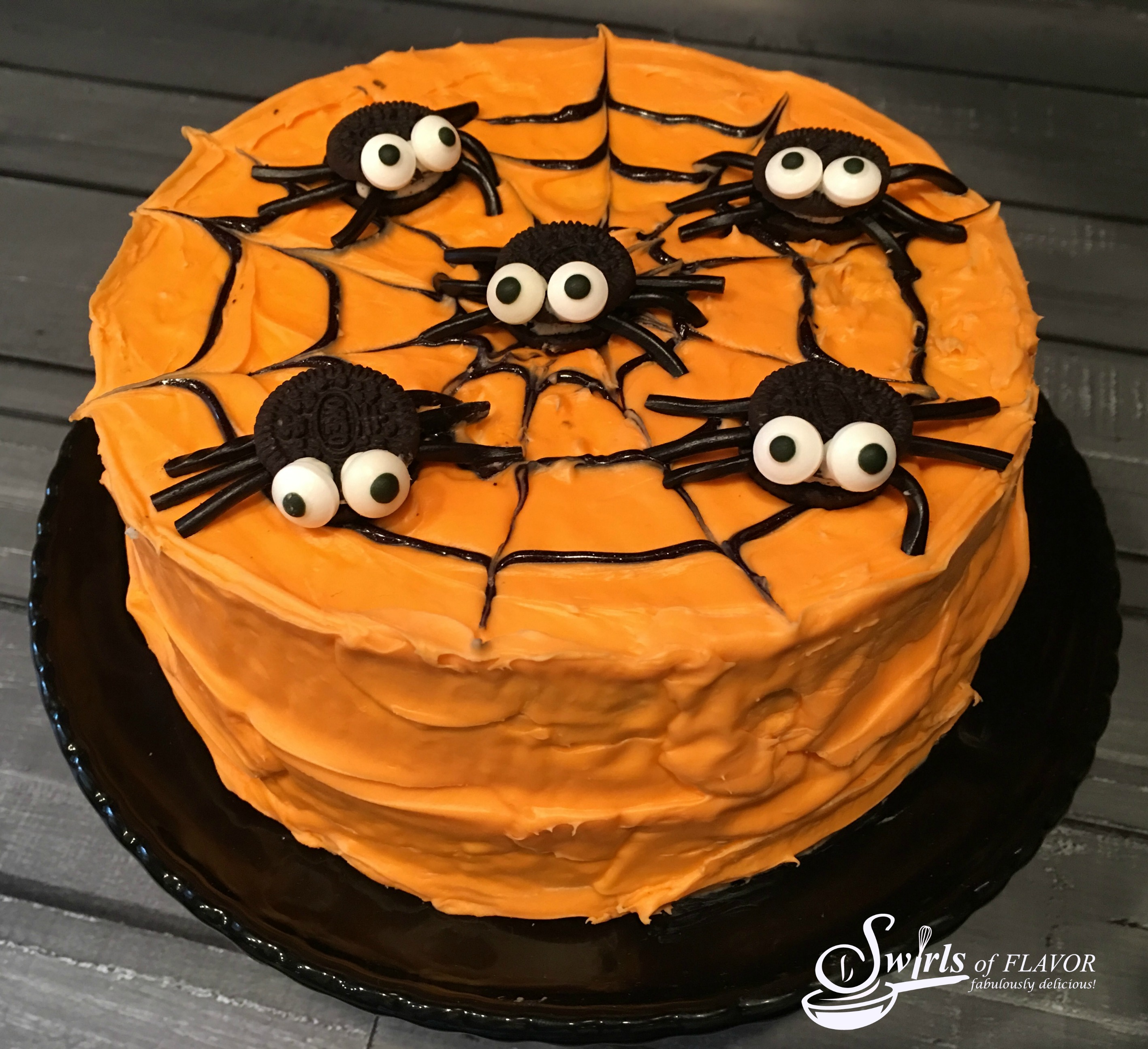 Cookie spiders on orange layer cake for Halloween