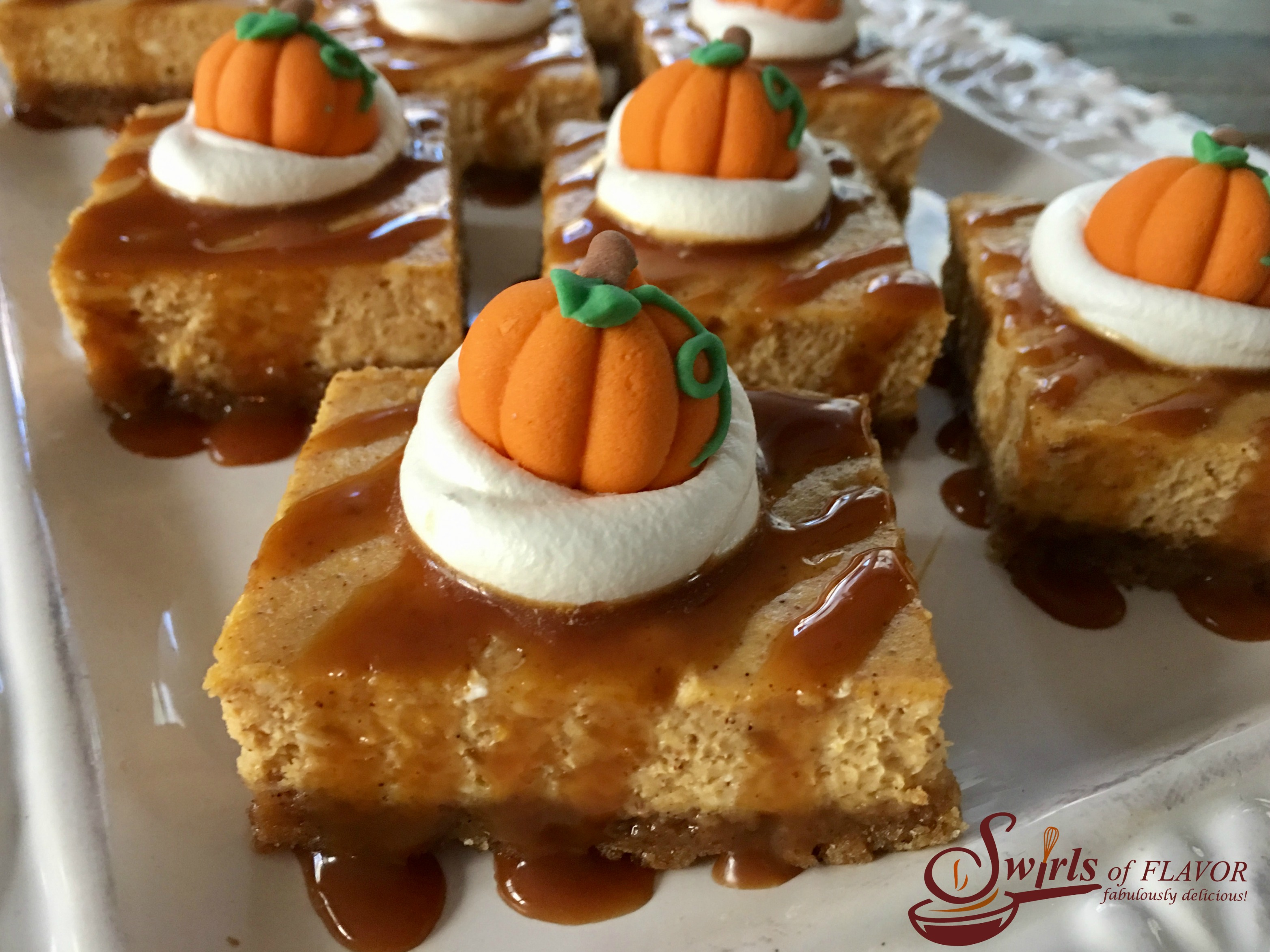 Salted Caramel Pumpkin Spice Cheesecake Bars is an easy way to make a cheesecake recipe without all the fuss. Every bite of these creamy cheesecake bars recipe is kissed by the warm holiday flavor of pumpkin pie spice and buttery cinnamon graham crust! And it's such an easy recipe to make and will impress your guests too! #pumpkinspice #pumpkincheesecake #cheesecakebars #easyrecipe #dessert #easydessert #holiday #saltedcaramel #pumpkincheesecakebars #pumpkinpuree #pumpkinpiespice #swirlsofflavor