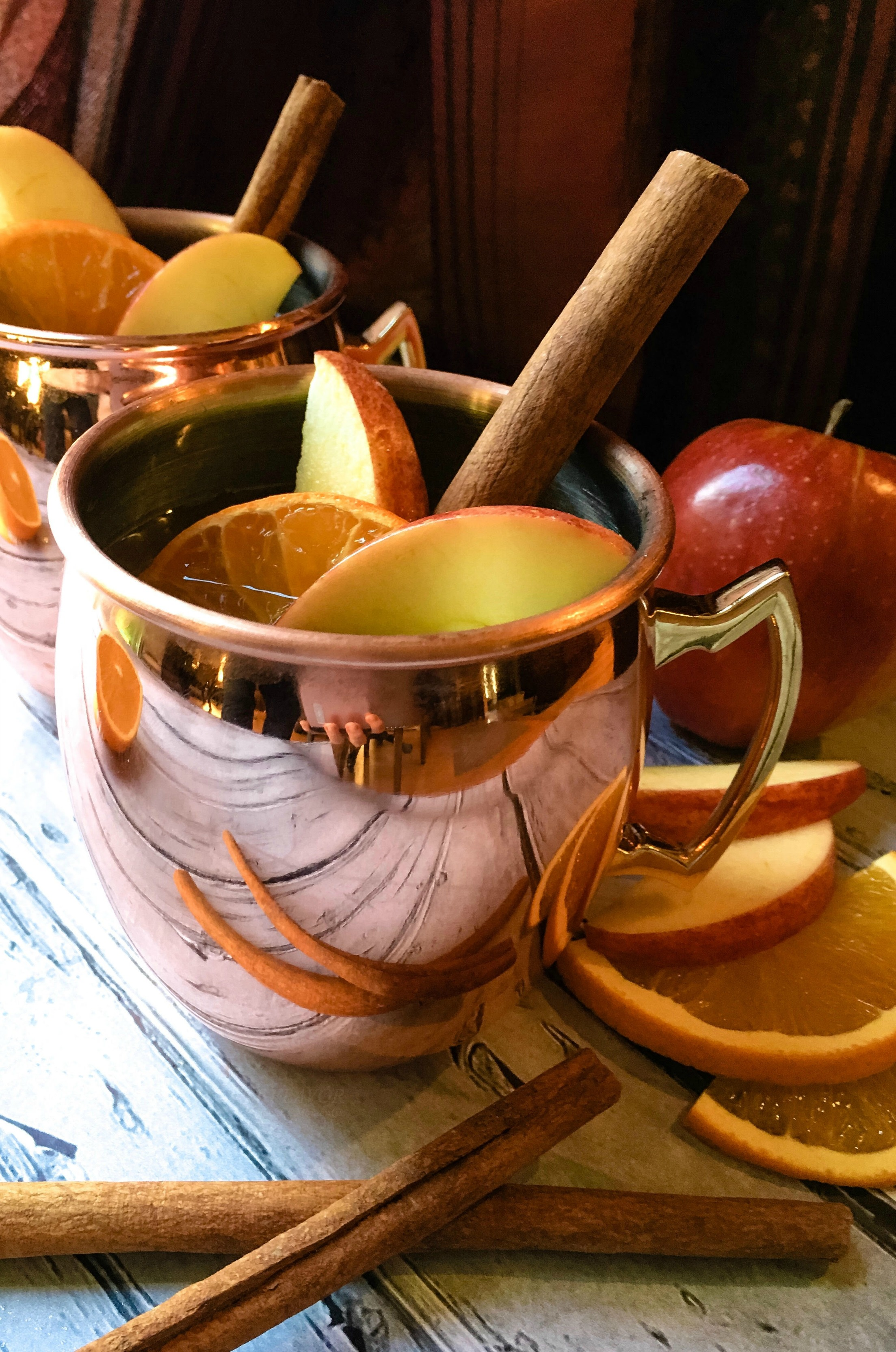 Apple Cider Moscow Mule in a copper mug with cinnamon stick and apple slices
