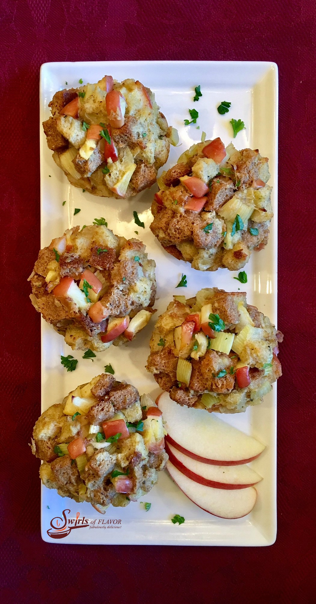 five stuffing muffins with fresh apple slices on platter
