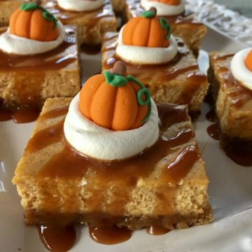 close up of pimpkin cheesecake bars with caramel sauce and whipped topping
