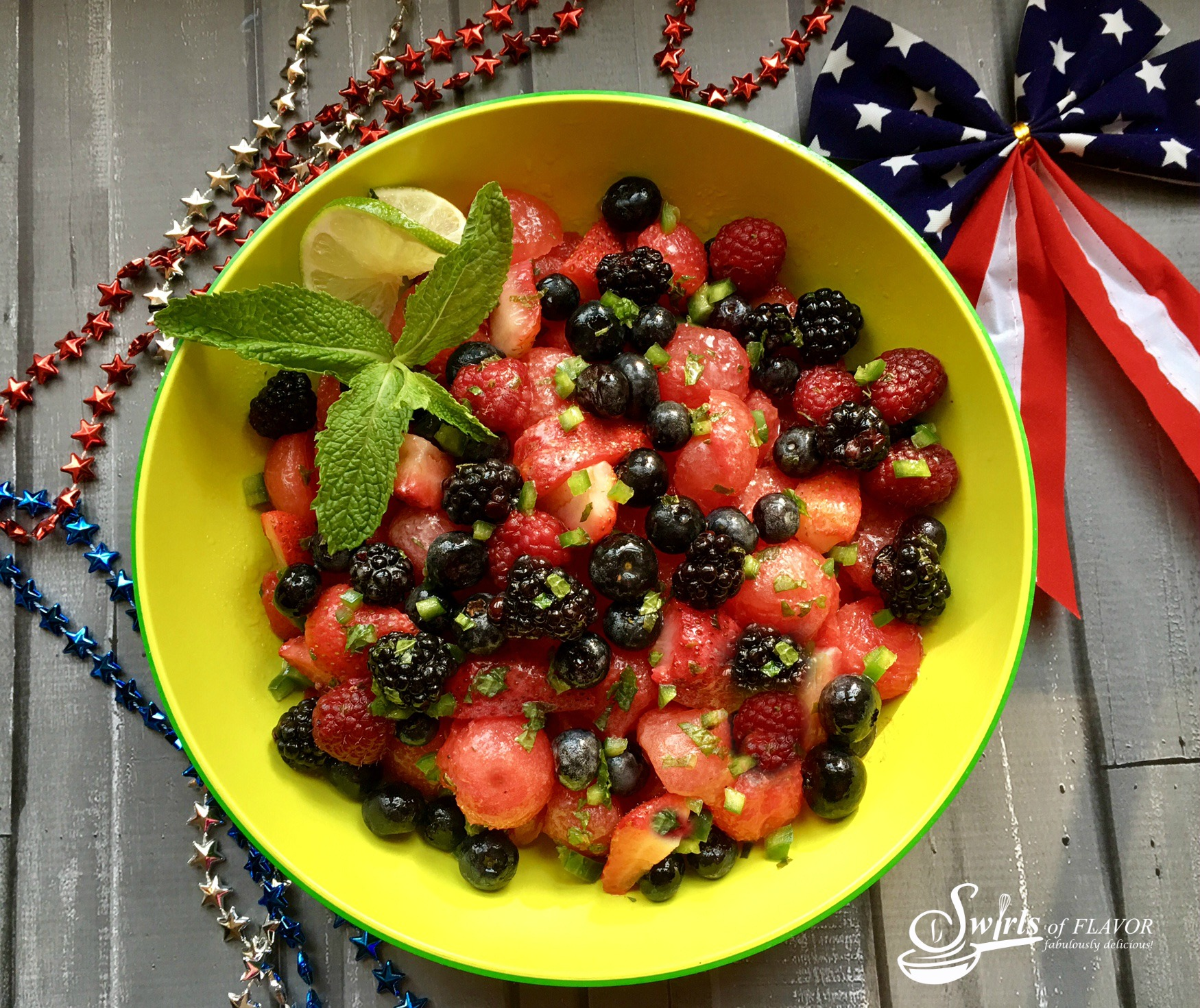 Jsummer fruit salad with watermelon, berries and fresh mint in a colorful bowl