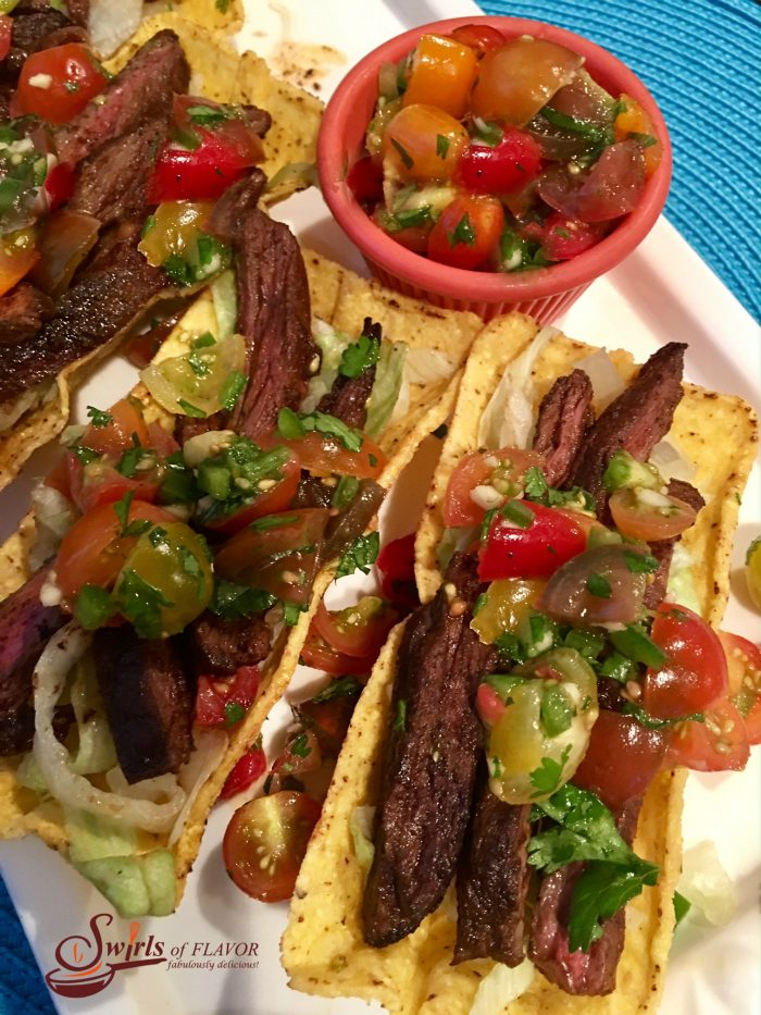 Seasoned slices of juicy skirt steak are nestled in a crunchy corn shell and topped with a lime-scented fresh heirloom tomato salsa. #tacos #TacoTuesday #steak #tacos #CincodeMayo #grilling #freshsalsa #swirlsofflavor #easyrecipe