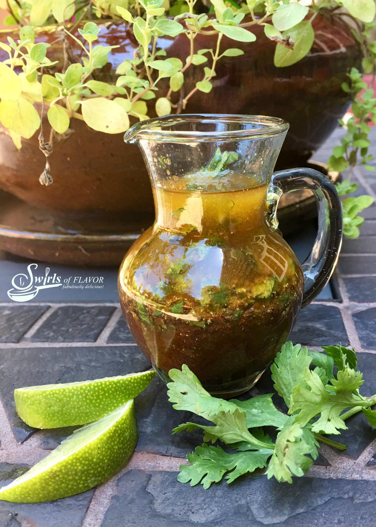 Cilantro Lime Vinaigrette in a cruet with fresh herbs