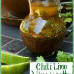 cruet of chili lime vinaigrette with lime wedges