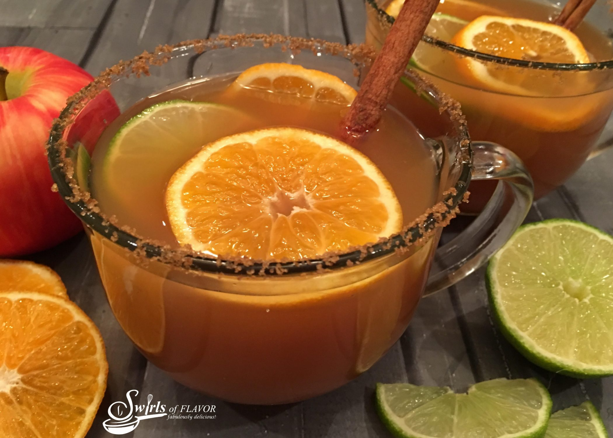Mulled Apple Cider in a clear mug with cinnamon sugar rims and frresh fruits and cinnamon stick