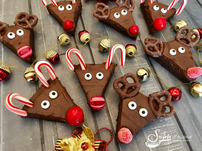 Reindeer Brownies is an easy recipe that will quickly become a holiday tradition and so much fun for kids! Fudgy homemade brownies topped with a silky-smooth cocoa buttercream frosting come to life as Rudolph with sugar eyes, candy cane antlers and a bright red candy nose, of course! #homemadebrownies #reindeer #holiday #Christmas #easyrecipe #Rudolphthe rednosedreindeer #funforkids #reindeerbrownies #cocoafrosting #candycane #swirlsofflavor