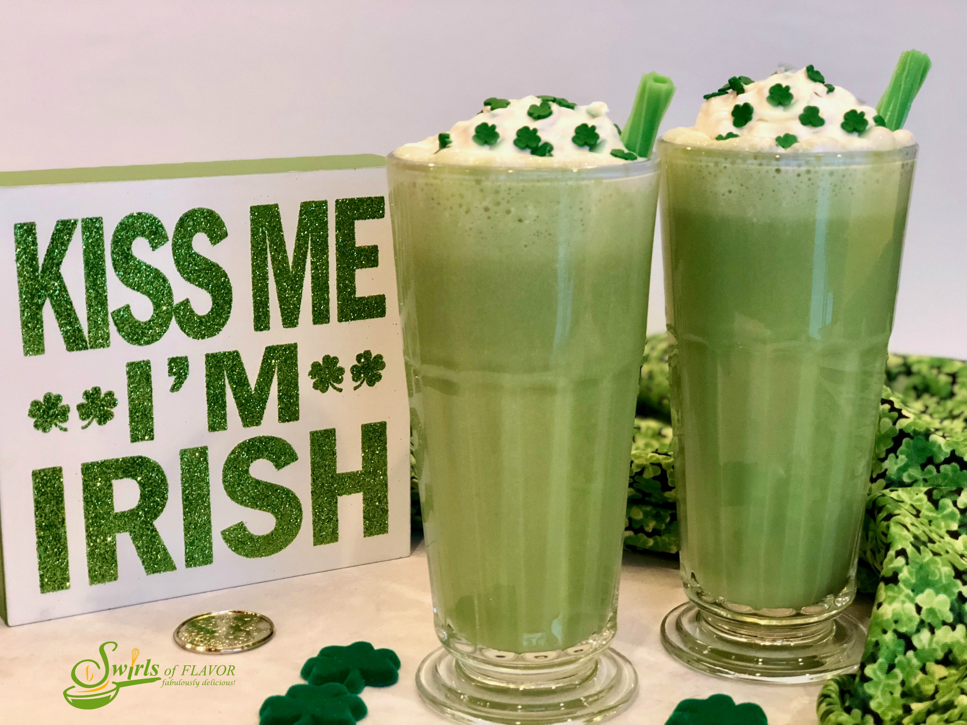 two shamrock shakes in tall glasses with green licorice straws