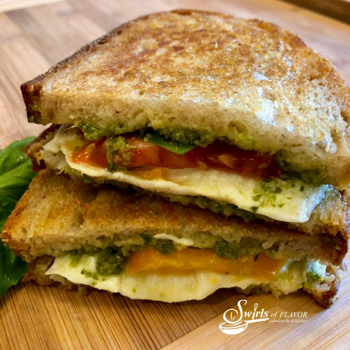 Caprese Grilled Cheese is bursting with fresh mozzarella, tomatoes, pesto, basil leaves, and of course, butter! A classic sandwich with an updated flavor! easy | grilled cheese | mozzarella | pesto | recipe | basil | tomatoes | #swirlsofflavor