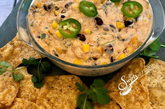 Creamy Corn and Black Bean Dip, an easy dip recipe that's bursting with cheesy goodness and a hint of spice, served with tortilla chips or fresh veggie dippers, is a delicious way to kick off your Cinco de Mayo fiesta! hot dip   corn   black bean   creamy dip   appetizer   party food   #swirlsofflavor