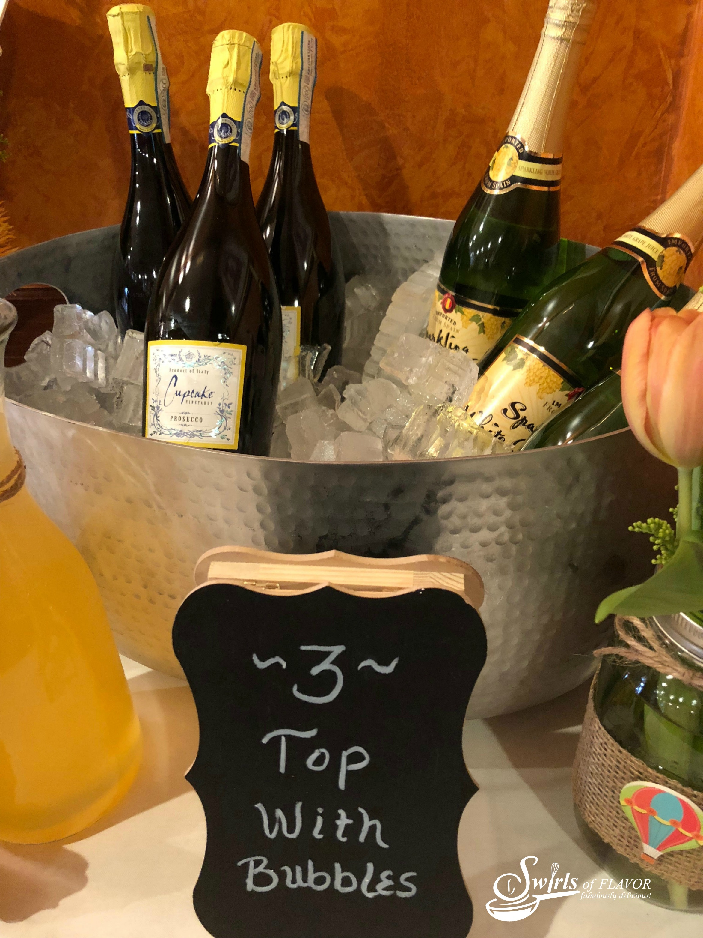 Prosecco and sparkling juice in bucket with ice and Top With Bubbles sign