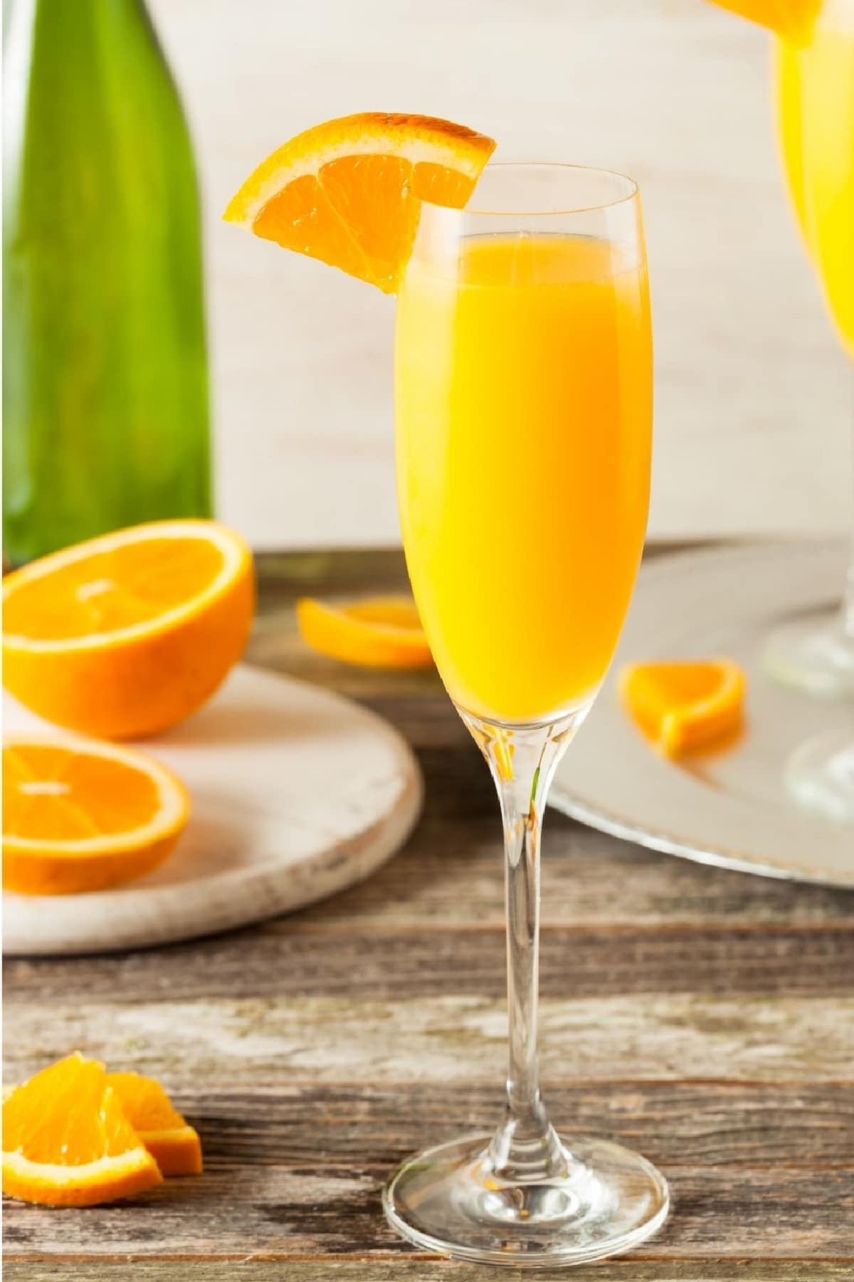 champagne flute filled with a mimosa cocktail and orange wedge garnish