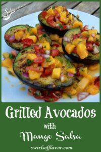Grilled avocados topped with frresh mango salsa on a white plate