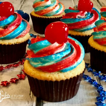 4th of July cupcakes are simple from-scratch vanilla cupcakes topped with a homemade buttercream frosting decorated with red and blue stripes and topped with a cherry. Perfect for your patriotic celebration!