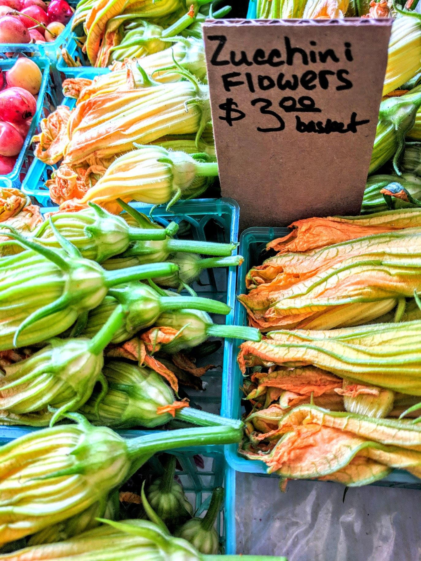zucchini flowers in baskets at farmers market