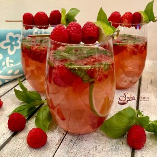 Basil Raspberry Rose Sangria is bursting with juicy raspberries, fresh basil, lime, Rose wine, vodka, raspberry liqueur and seltzer for a light fruity summertime sangria. #easyrecipe #summersangria #cocktails #drinks #rosesangria #sangria #rosewine #raspberries #basil #lime #vodka #raspberryliqueur #happyhour #swirlsofflavor