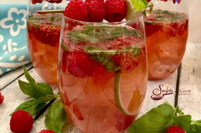 Basil Raspberry Rose Sangria is bursting with juicy raspberries, fresh basil, lime, Rose wine, vodka, raspberry liqueur and seltzer for a light fruity summertime sangria. #easyrecipe #summersangria #cocktails #drinks #rosesangria #sangria #rosewine #raspberries #basil #lime #vodka #raspberryliqueur #happyhour #swirlsofflavor