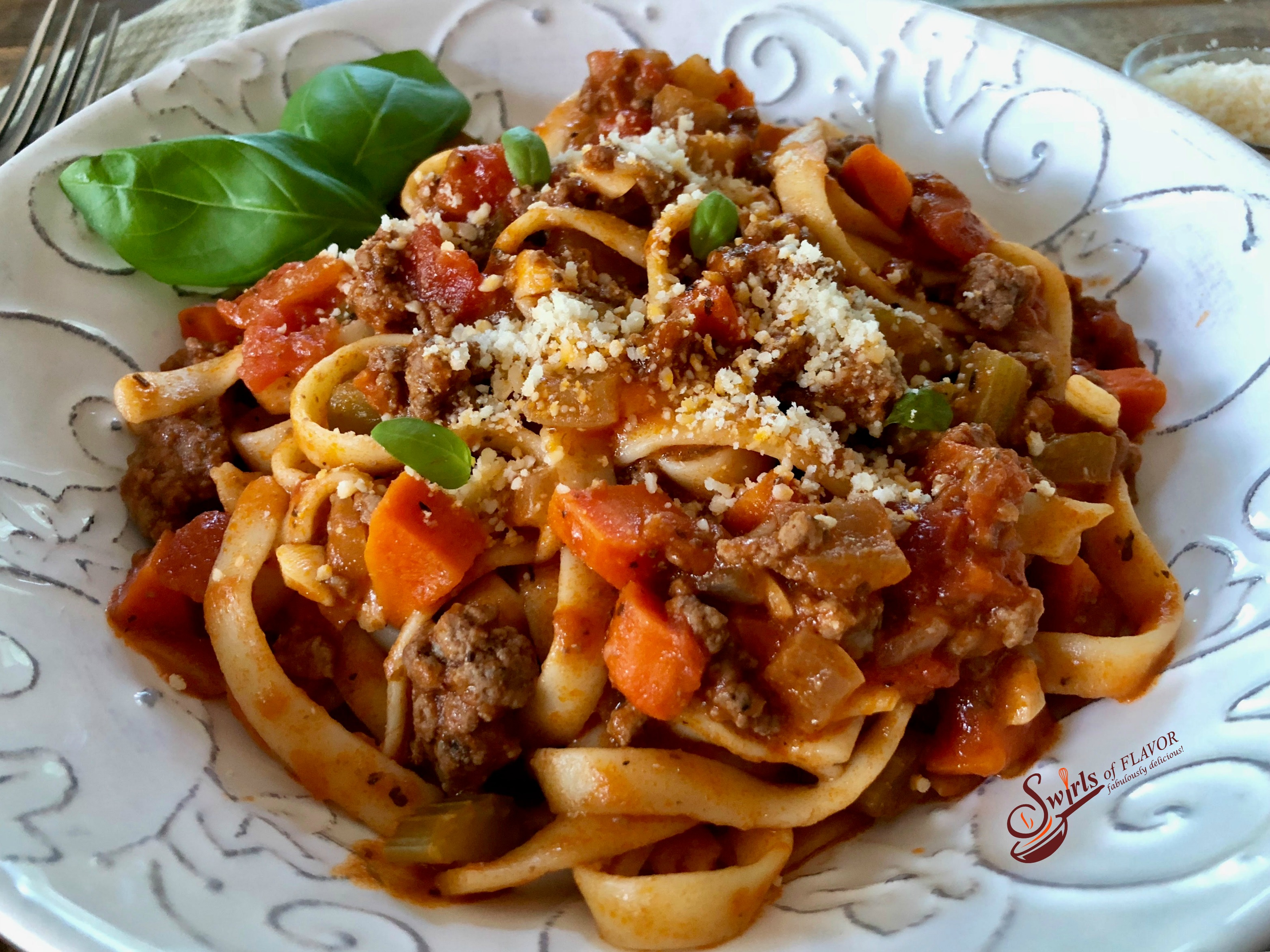 close up of a bowl of pasta with bolognese sauce, grated cheese and fresh bsil leaves