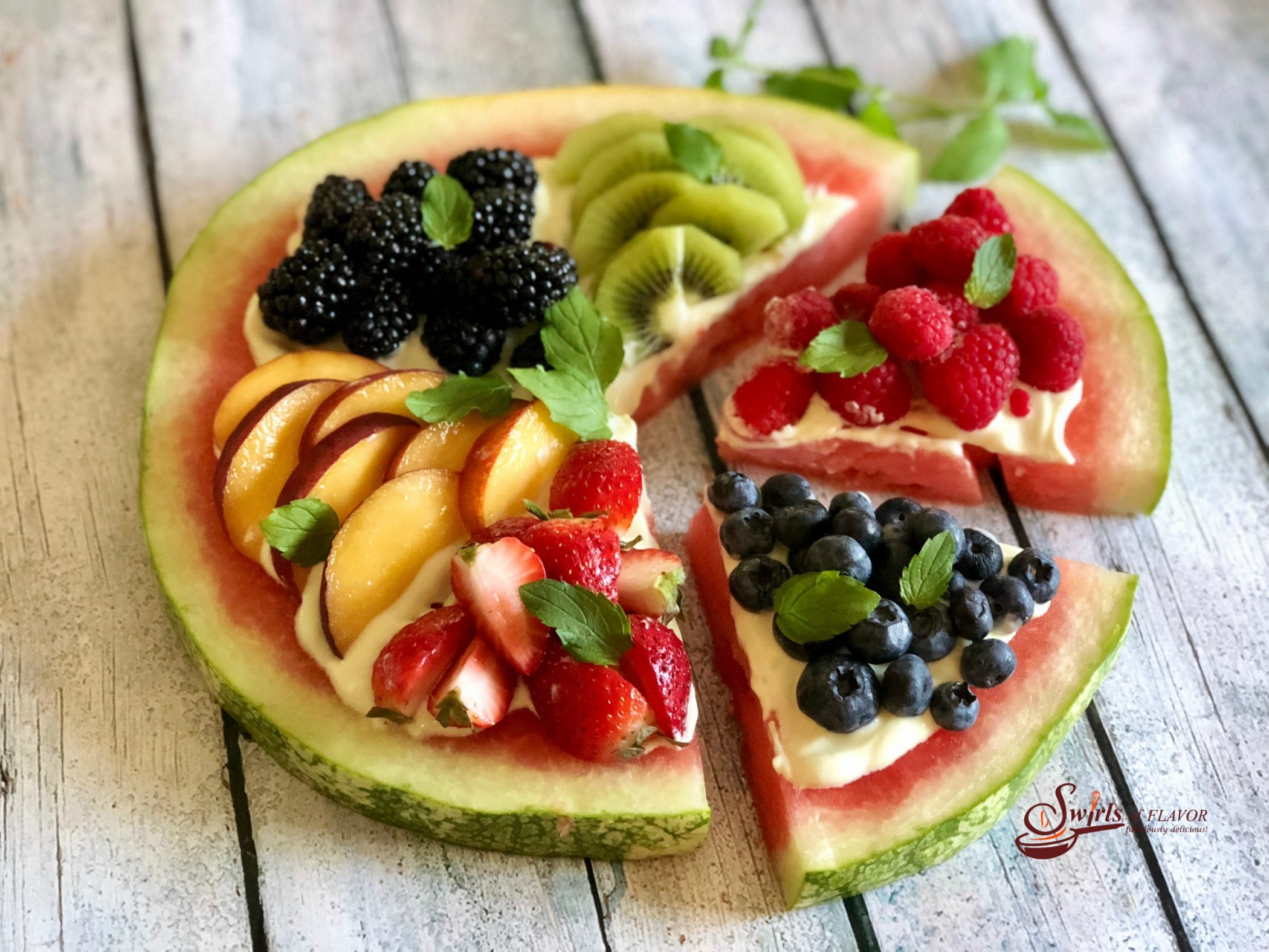 Watermelon pie topped with fruit and two slices cut