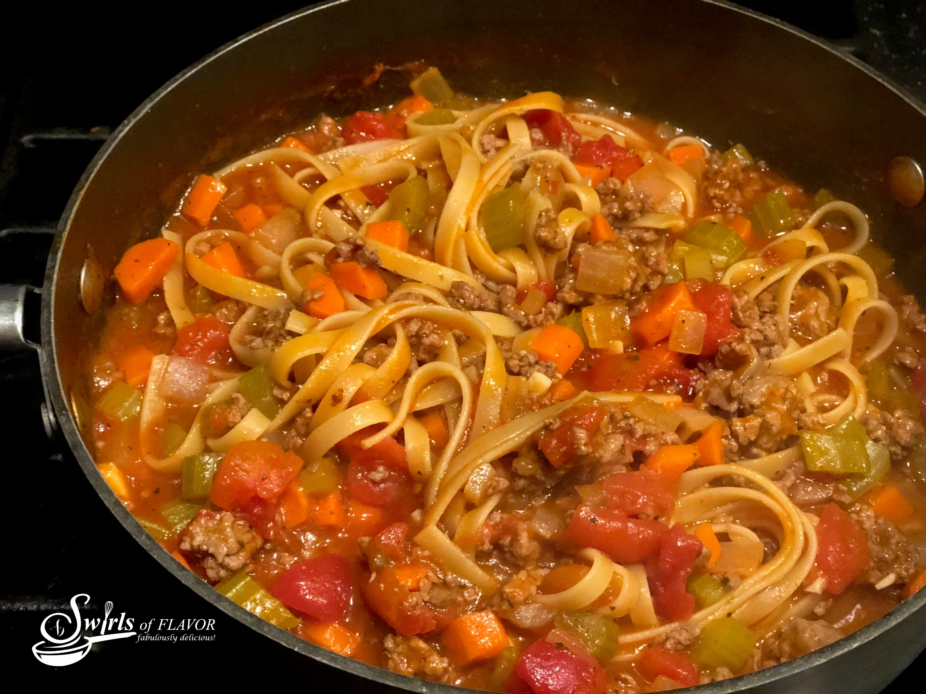 fettuccine bolognese recipe cooking in a skillet with deep sides