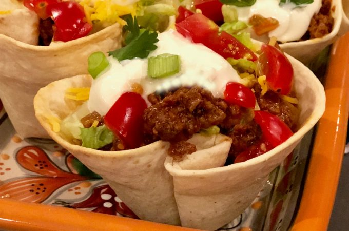 Beef Taco Cups is an easy recipe that makes Taco Tuesday even more fun and delicious than before. Tortillas bake for just ten minutes in a muffin tin to form crunchy cups that are filled with a flavorful saucy beef mixture and topped with shredded cheese, lettuce, sour cream, scallions and cilantro. Fun for kids and grown ups too, Beef Taco Cups will soon become your favorite way to celebrate Taco Tuesday! #tacos #tacocups #groundbeef #tacotuesday #funforkids #easyrecipe #tortillacups #swirlsofflavor