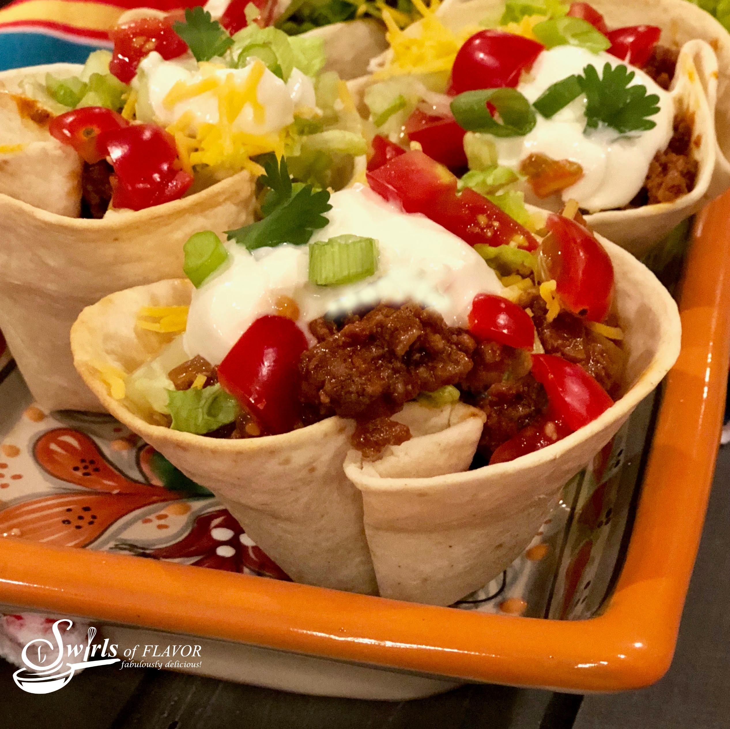 ground beef tacos in tortilla shells with taco toppings