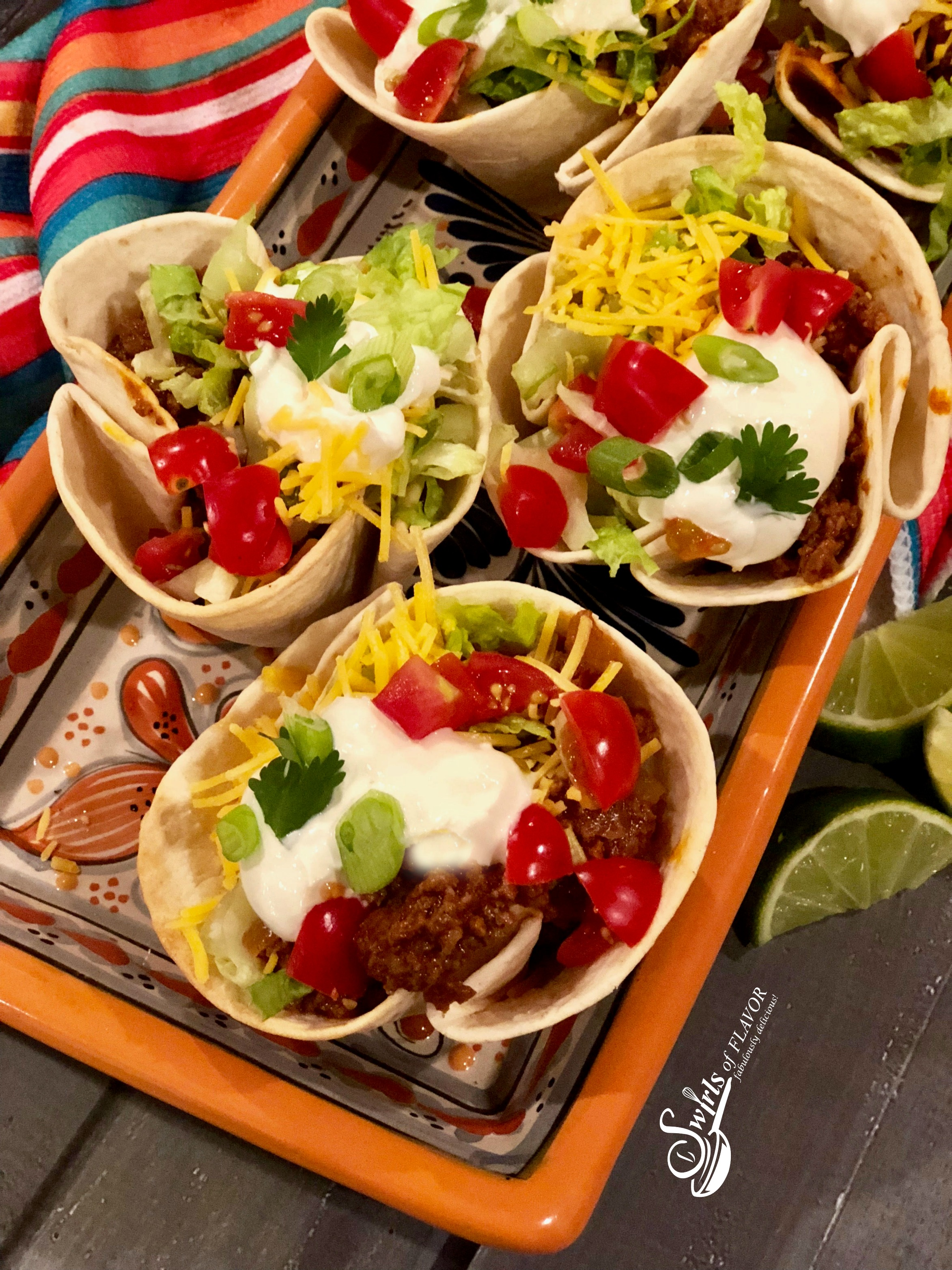 Beef taco cups with taco toppings in colorful dish