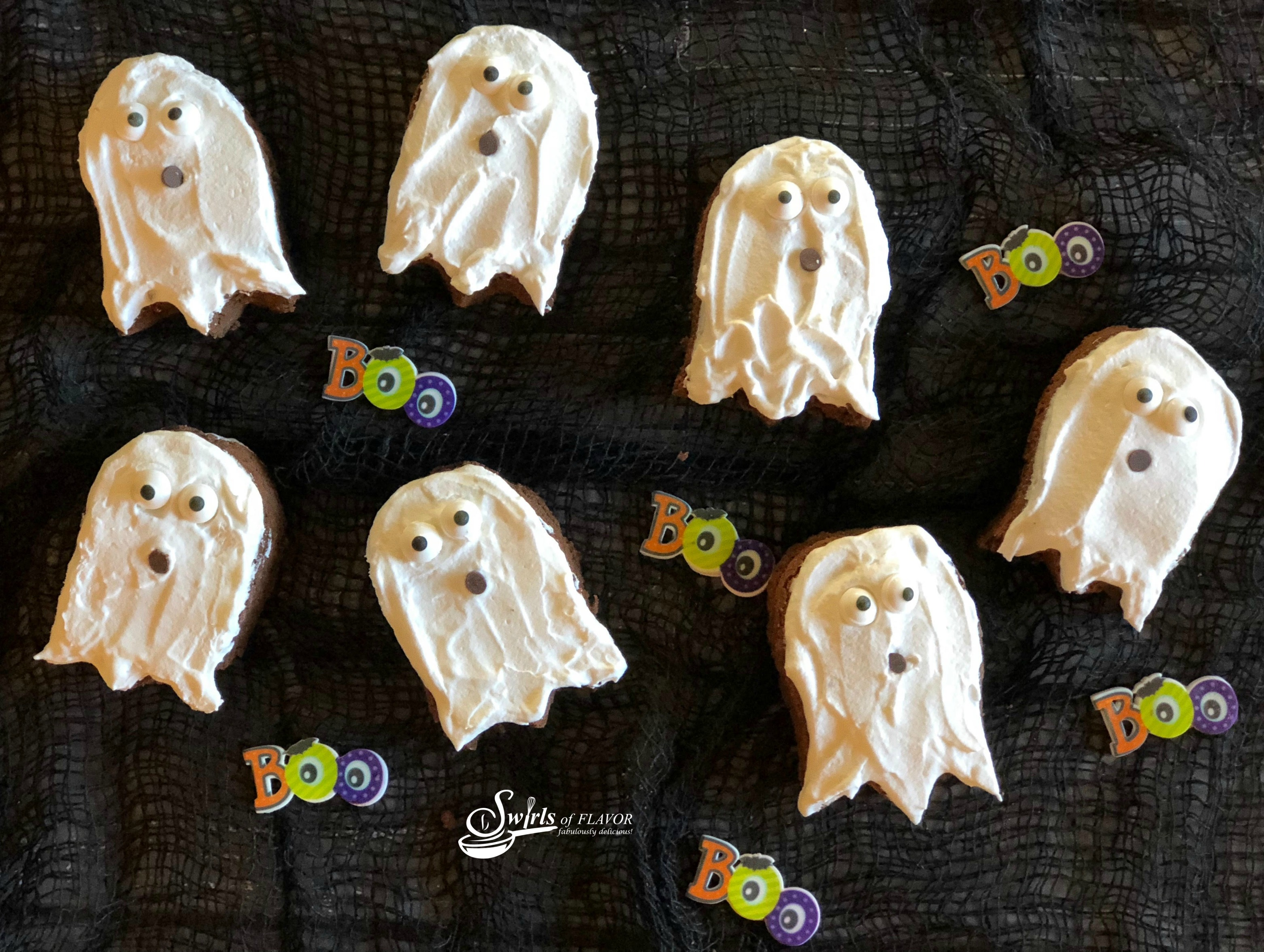 brownies shaped like ghosts with whipped topping and sugar eyes