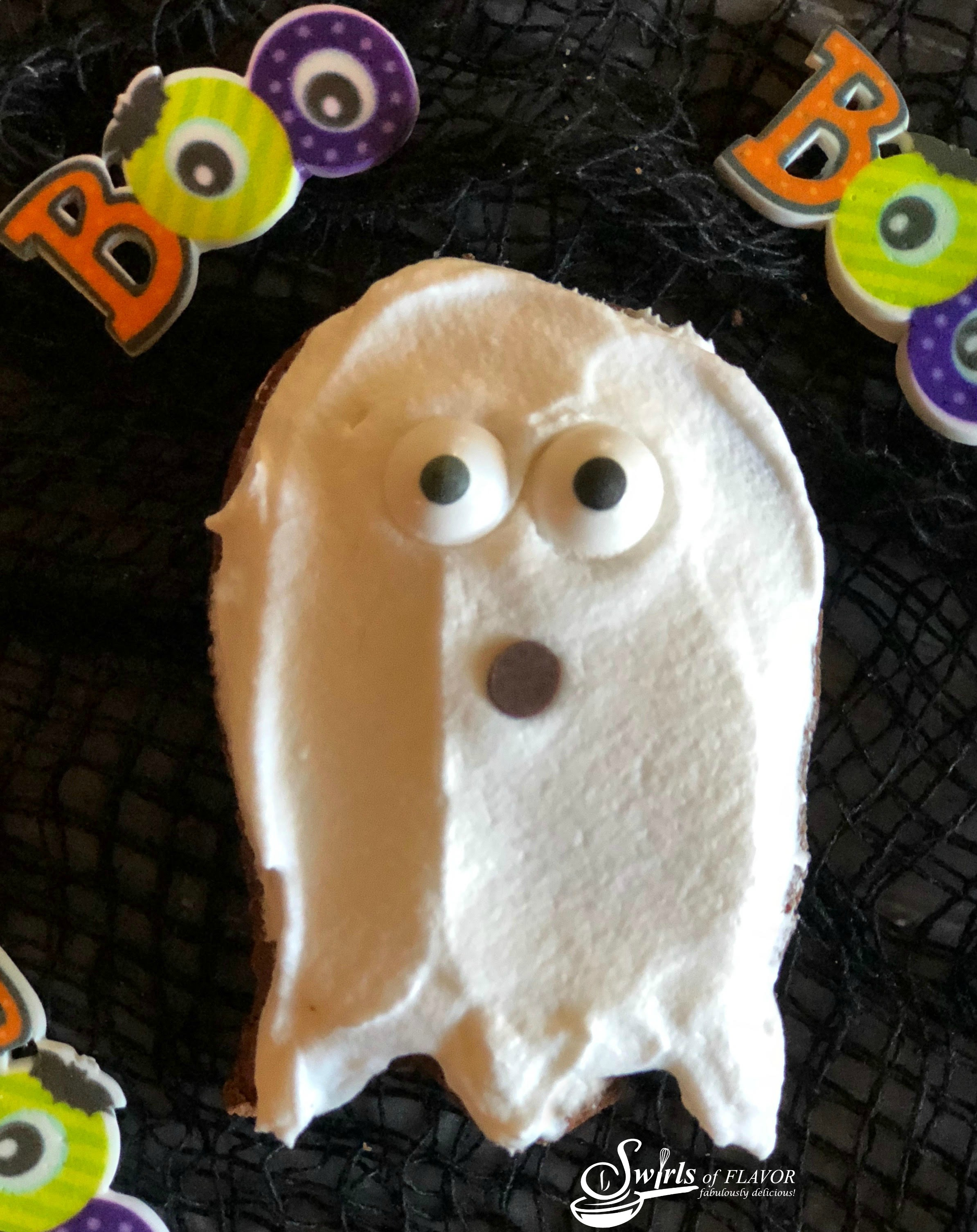 a brownie in the shape of a ghost with sugar eyes and chocolate chip mouth