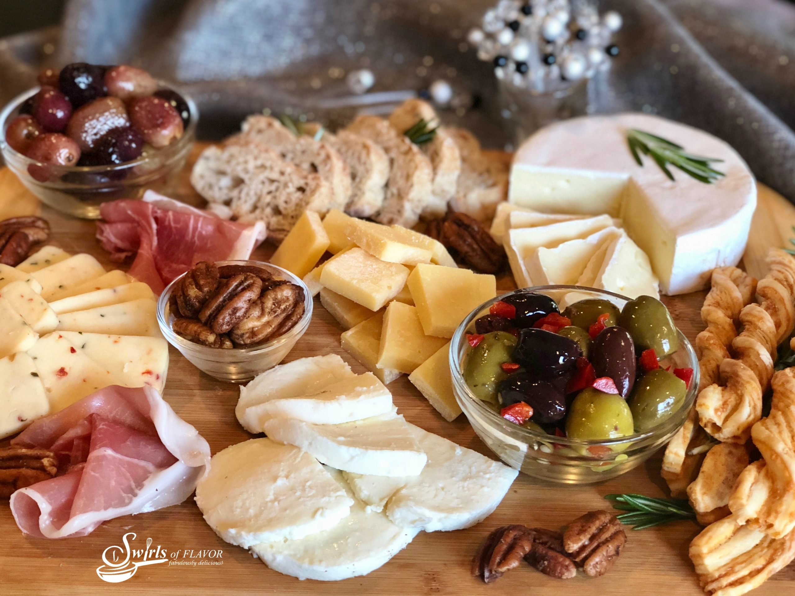 A Holiday Cheese Board is an impressive appetizer or even a dessert when it's filled with assorted cheeses, ciabiatta bread, mixed olives, roasted grapes and spiced pecans. Easy to assemble, Our Holiday Cheese Board will be the center piece of your table with it's unexpected Balsamic Roasted Grapes and Buttery Spiced Pecans! #cheeseboard #holiday #entertaining #roastedgraped #spicedpecans #cheese #newyearseve #christmas #easyrecipe #swirlsofflavor