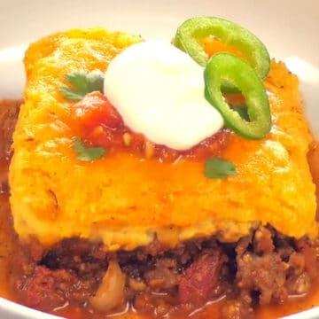 scoop of chili cornbread casserole with sour cream and scallions