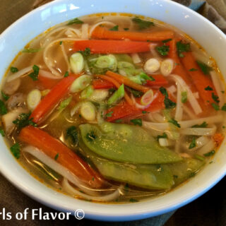 white bowl of Thai ginger soup with fresh vegetables