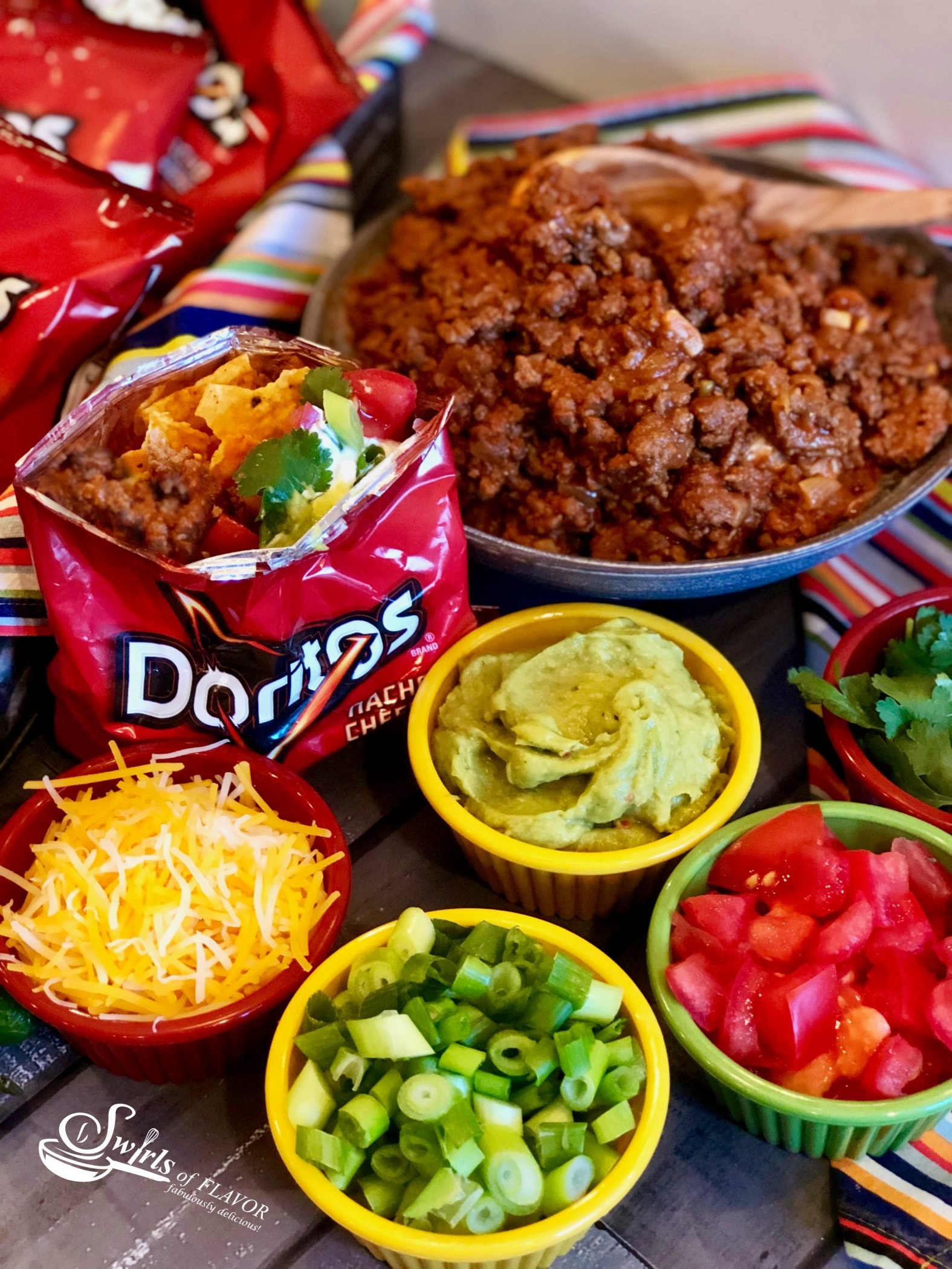 Walking Taco Bar ingredients in bowls with Doritos bag
