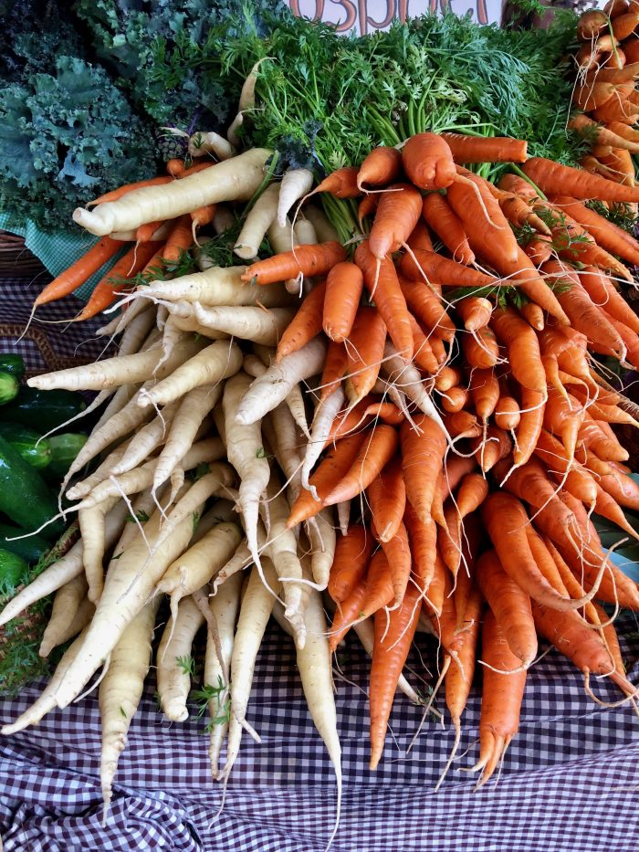 Fresh orange carrots and white carrots with green tops.