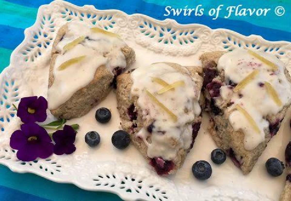 Ginger Glazed Blueberry Scones on white platter with fresh blueberries