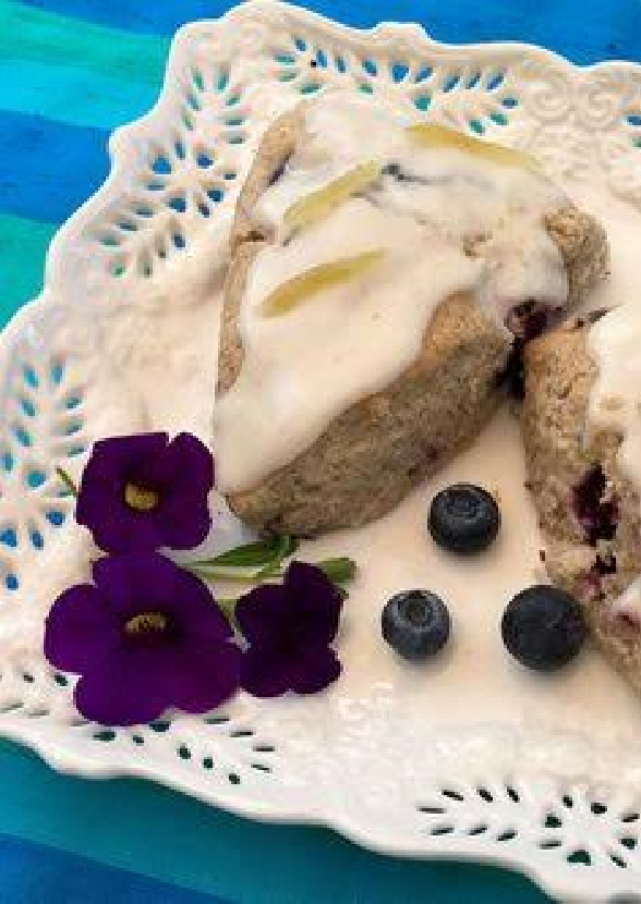 a blueberry scone with edible flowers on white platter