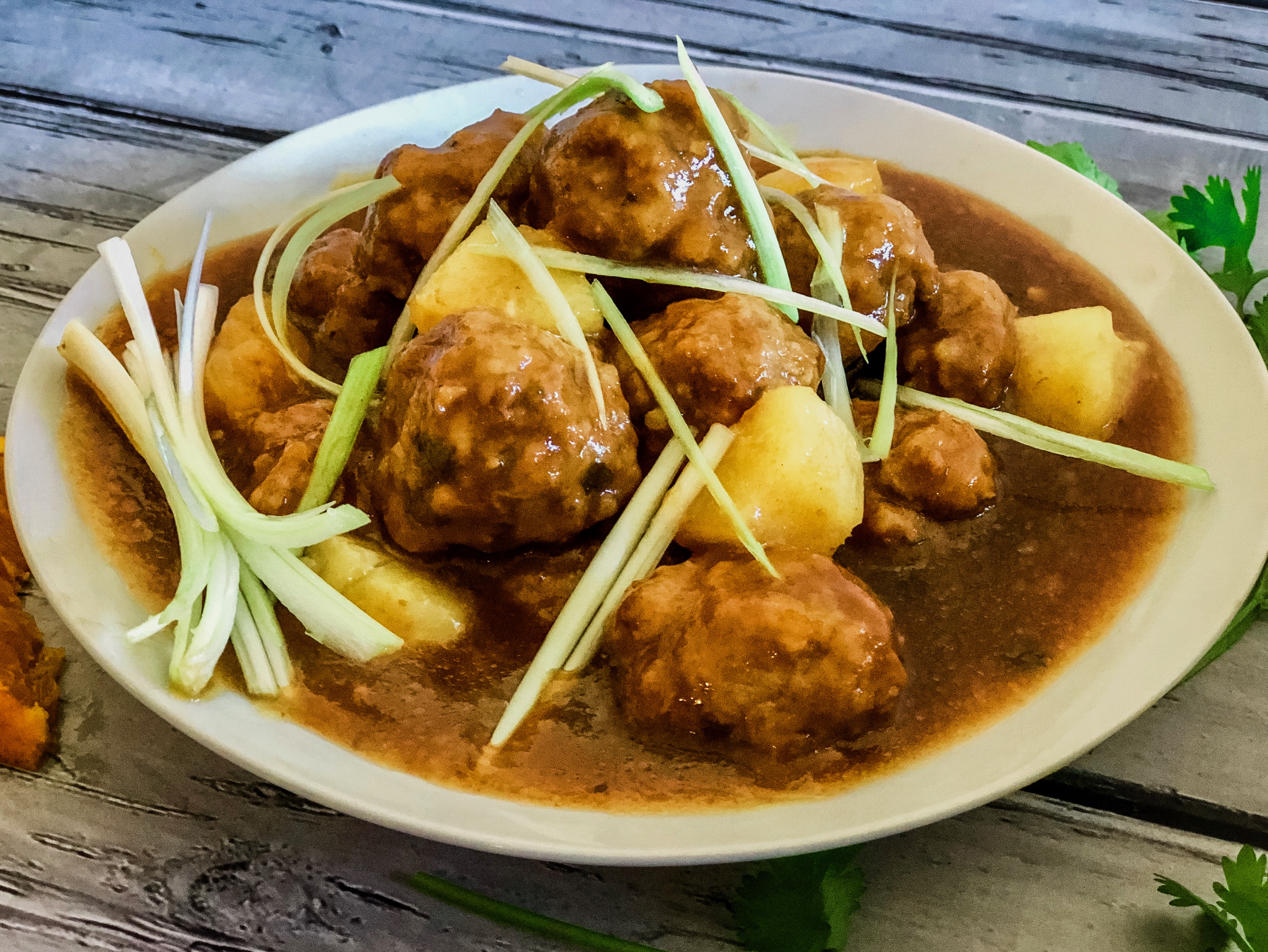 bowl of sweet and sour mini meatballs with scallions