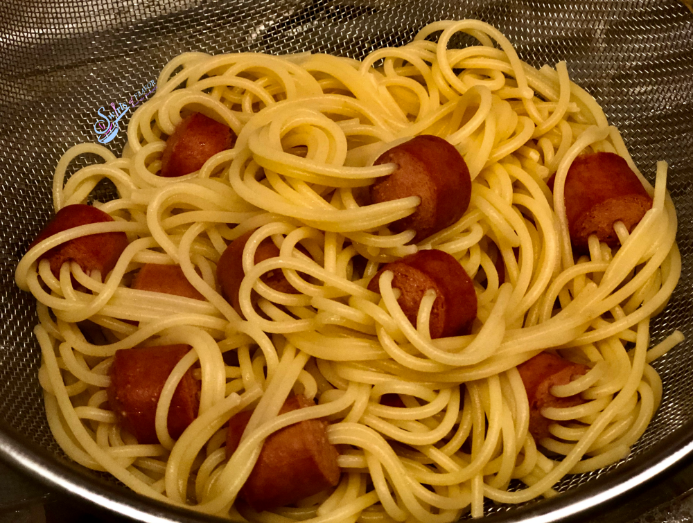 cooked hot dogs with spaghetti in strainer