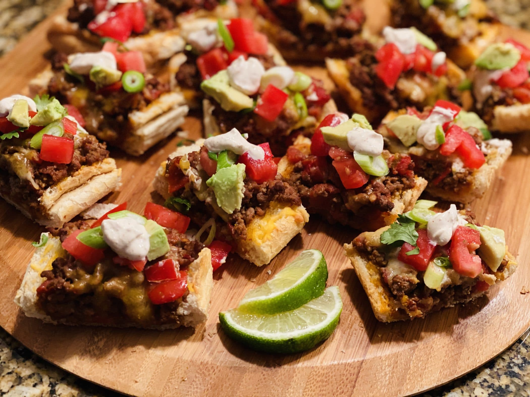 appetizer size servings of taco bread on a wooden board with lime wedges