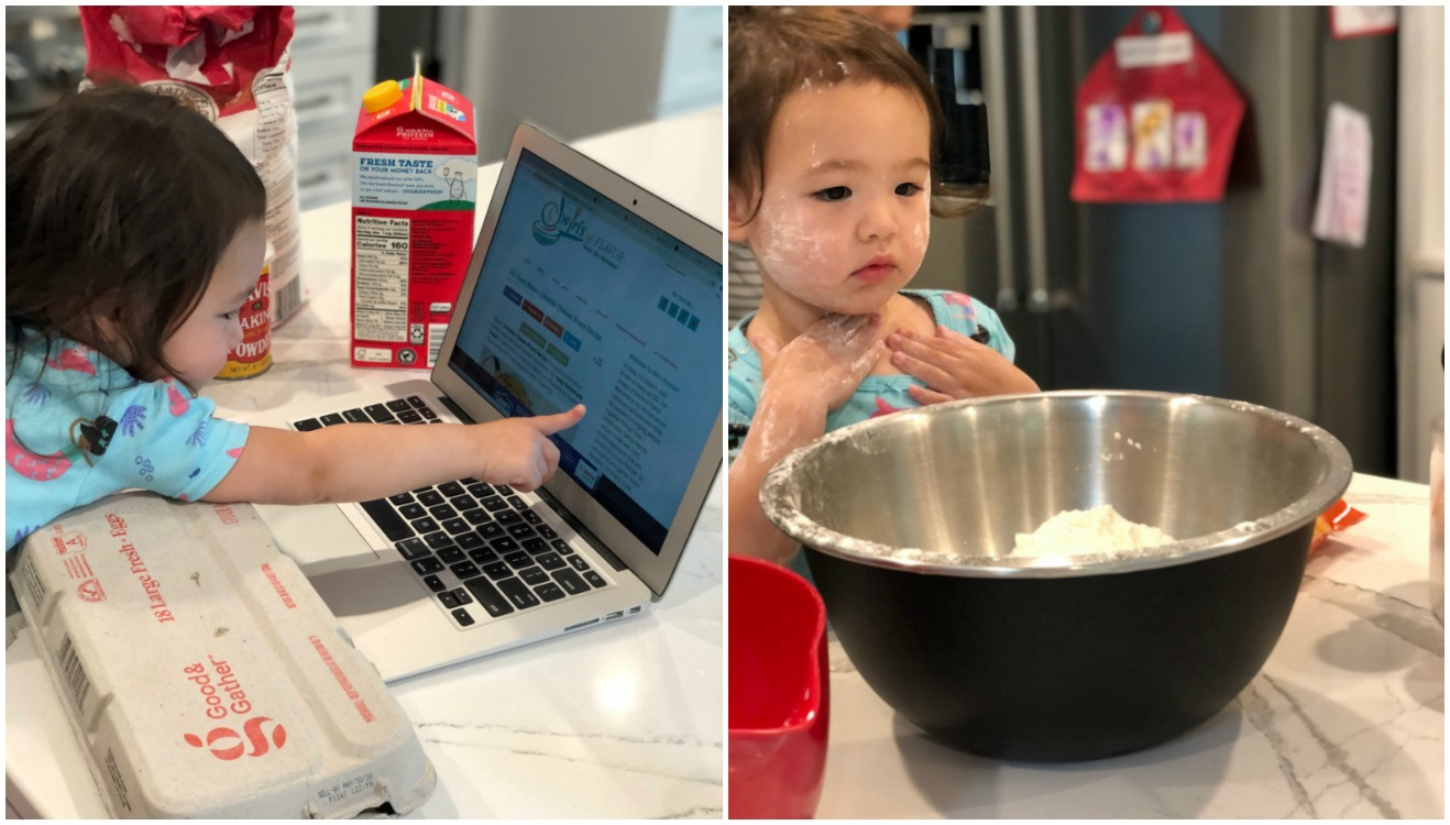 Little girl looking at computer and little girl with flour on her face and bowl of flour