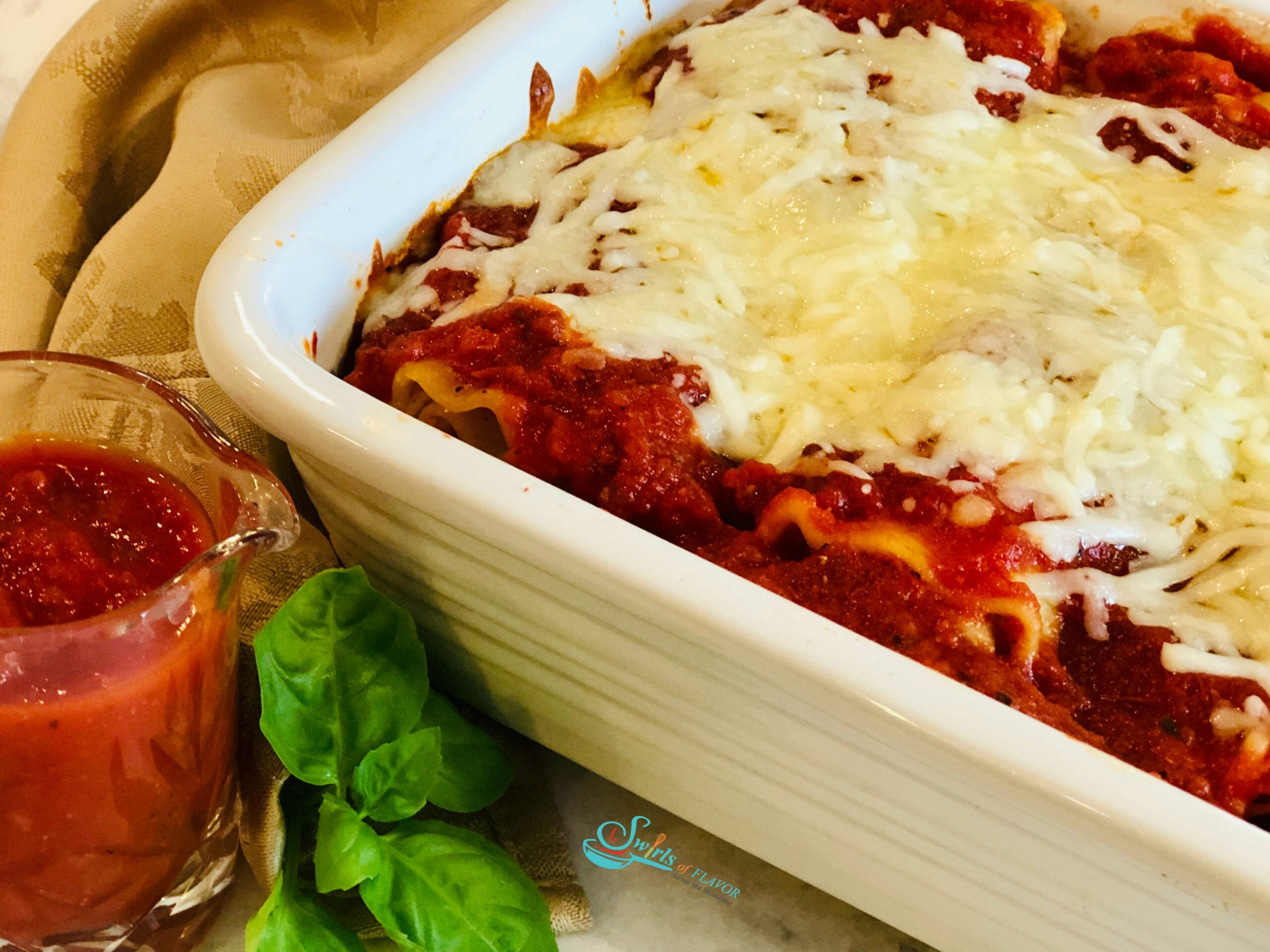 Lasagan Roll ups in white baking dish with pitcher of sauce and fresh basil
