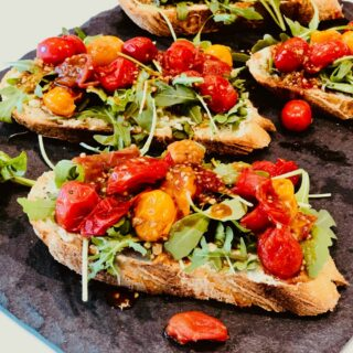Tomato and arugula on toast on grey slate