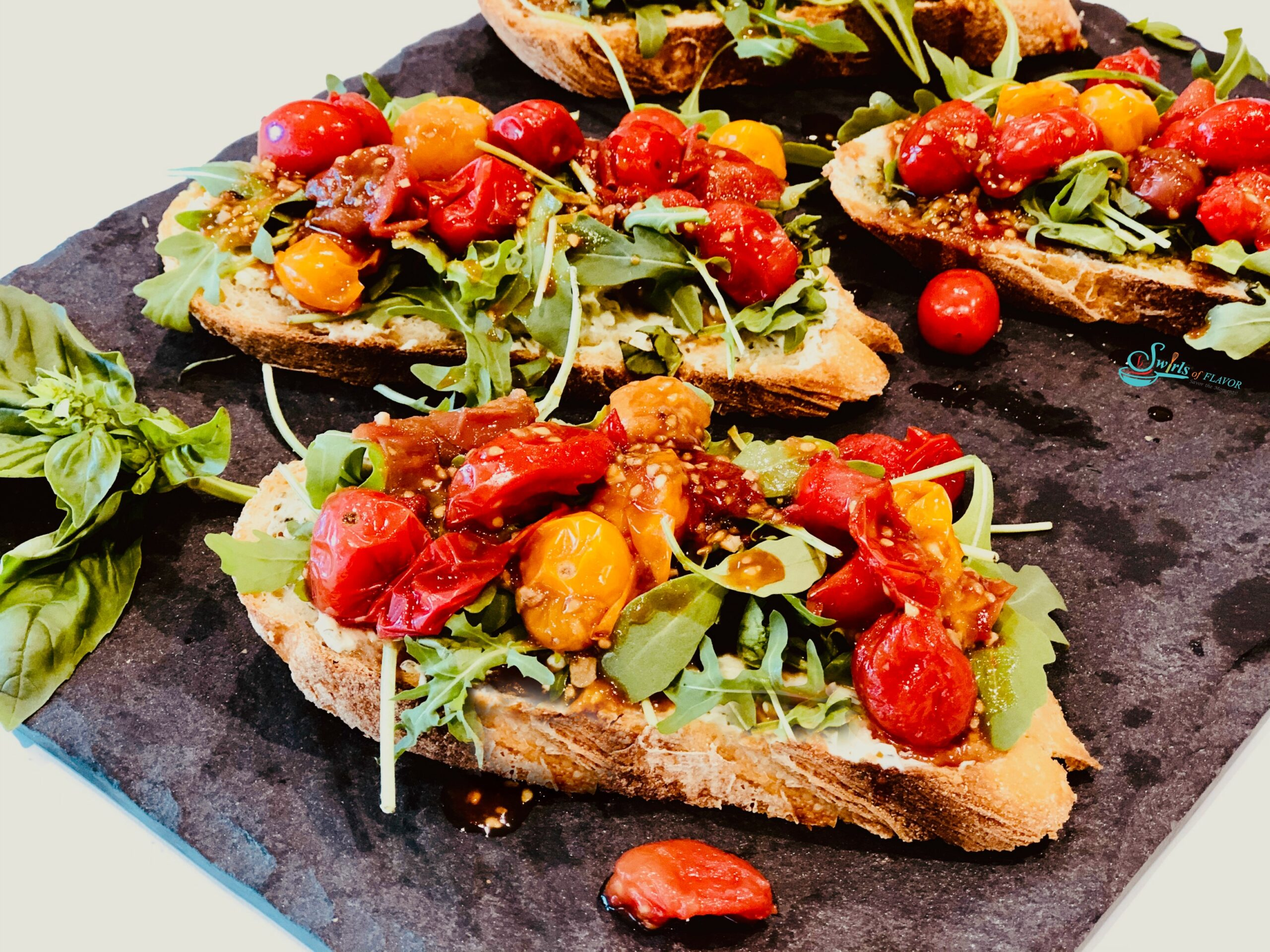 Close up photo ofBreakfast toasts with blistered tomatoes and arugula on grey slate surface
