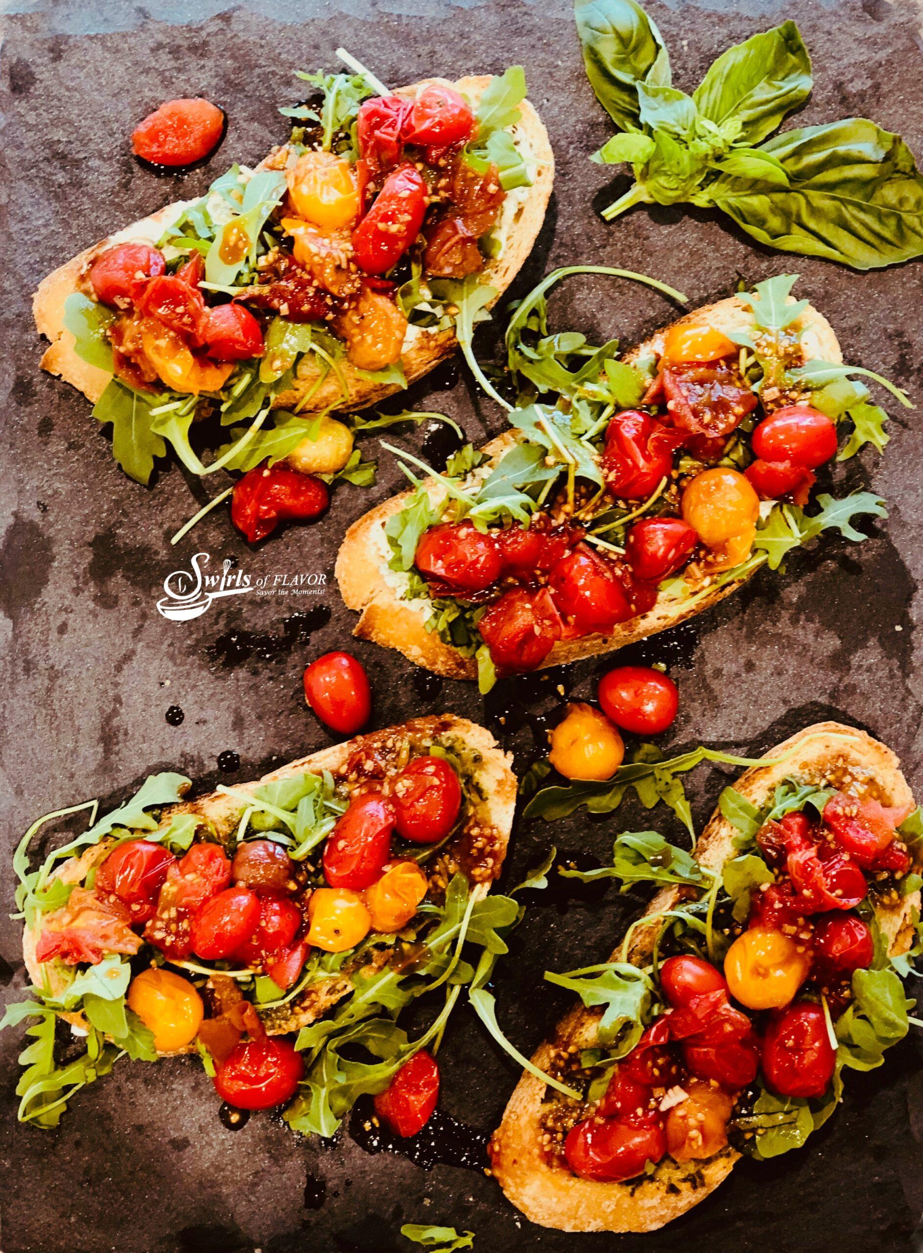 Ovrhead photo of four tomato and arugula toasts with fresh basil on a grey slate