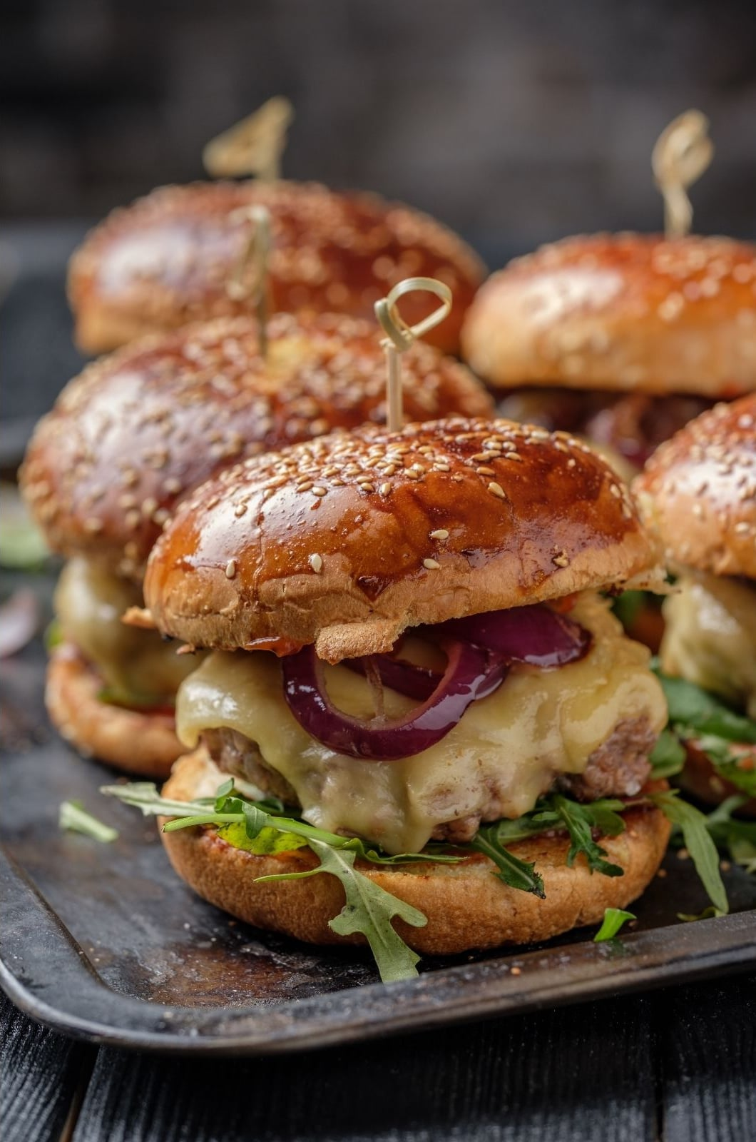 French onion hamburgers with melted cheese, red onions and arugula
