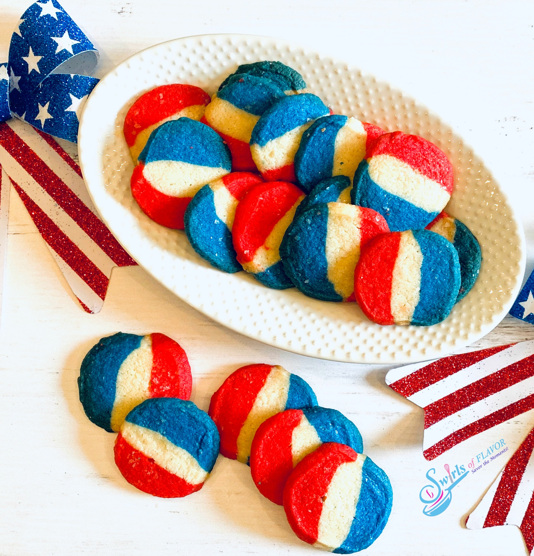 Red white and blue cookies on white oval platter and stacked in front
