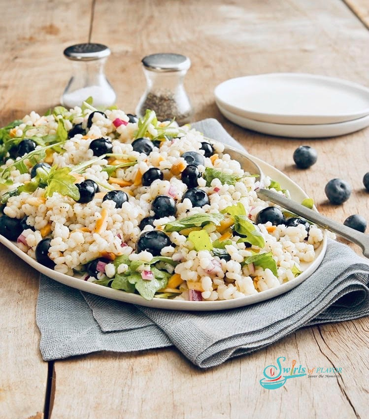 Barley Salad with baby greens and salt and pepper shaker on a white oval platter